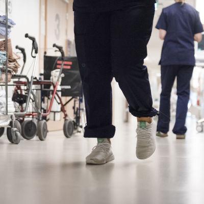 Sjukskötare går i en sjukhuskorridor. Man ser bara fötter och ben.