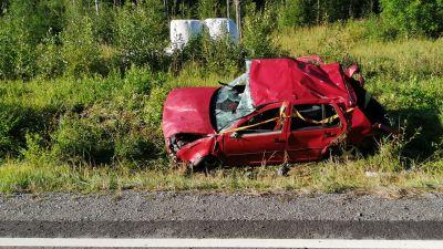 En röd personbil som varit med om en trafikolycka ligger i diket.