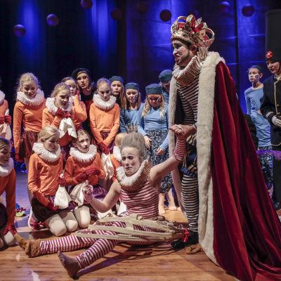 Scen ur Dumma kungen. Barn i ring runt ledsen kung och kvinna som sitter på golvet.