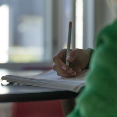 Lapsi tekee matematiikan tehtäviä kirjaan kotona.