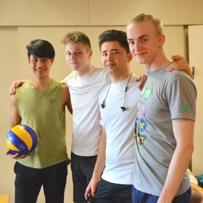 Fyra volleybollspelare med händerna på varandras axlar i träningsutymmet. en har bollen i handen.