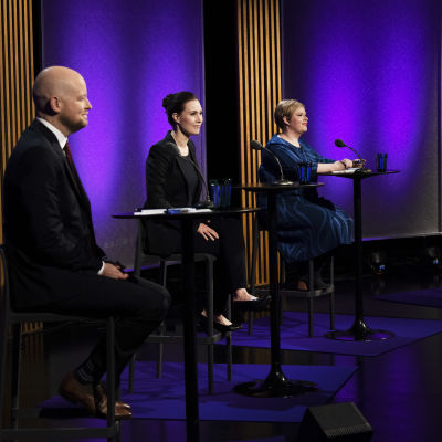 En man och tre kvinnor sitter i ett storm rum med blå golv och väggar. Från vänster undervisningsminister Jussi Saramo (VF), statsminister Sanna Marin (SDP),  Annika Saarikko ja Maria Ohisalo