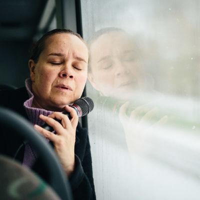 Katja Küttner istuu bussissa ja nojaa uupuneena, silmät kiinni ikkunaan. Kädessään hänellä on mikrofoni.