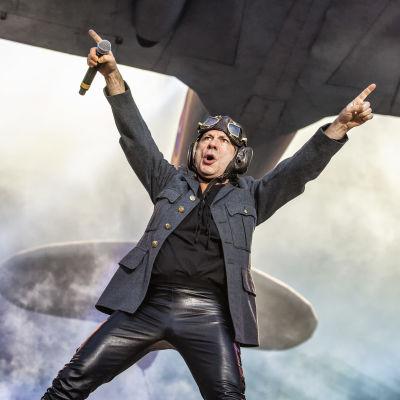 En äldre man i läderbyxor och flygarmössa på en scen.