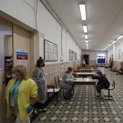 Personer med munskydd och skyddande kläder i en vallokal, en lång korridor.