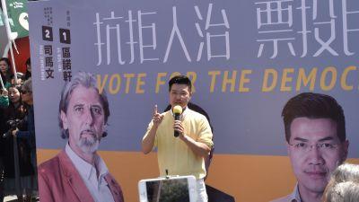 En person talar i en mikrofon framför ett valplakat.
