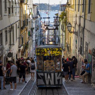 En spårvagn åker upp för en brant backe i Lissabons historiska centrum.