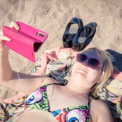 Jenni Hänninen katselee videota rannalla.