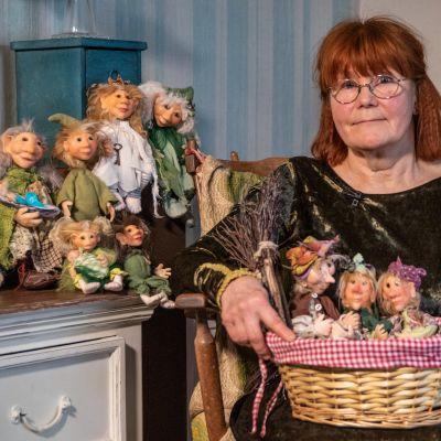 Iiris Nykänen istuu tuolilla sylissään kori, jossa on kolme koristeellista mettästonttunukkea. Naisen takana on kaksi lipastoa, joiden päällä on lisää nukkeja.