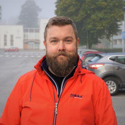 Man i skägg och orange jacka står på en gata.