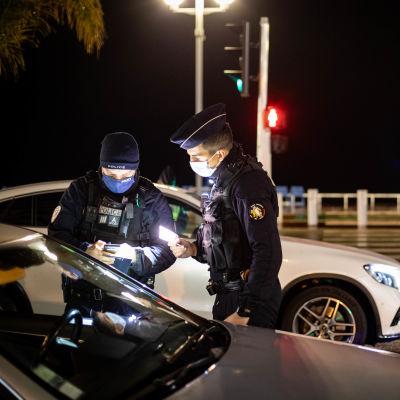 Franska poliser står vid en bil i mörkret, de kollar förarens dokument.