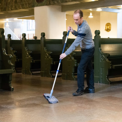 En man moppar golvet i Borgå domkyrka.