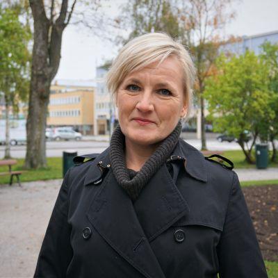 Blond kvinna i svart jacka står i en park.