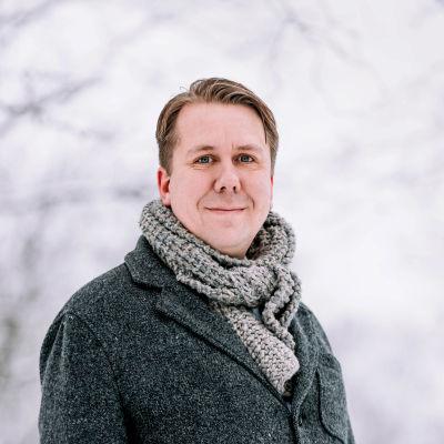 Mies seisoo lumisessa maisemassa ja katsoo kameraan