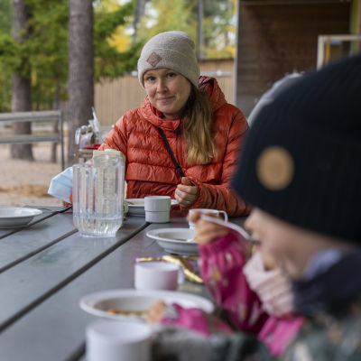 Juulia Jantunen, varhaiskasvatuksen opettaja, päiväkoti Kanavan pihalla syömässä lasten kanssa lounasta