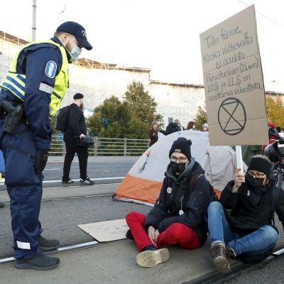 En polis står och talar med två Elokapina-demonstranter som sitter på gatan.