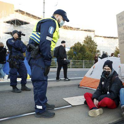 Poliiseja siirsi Elokapinan mielenosoittajia busseihin Mannerheimintiellä Helsingissä 2. lokakuuta 2021.