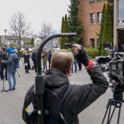 Toimittajia ja kuvaajia rakennuksen edustalla.