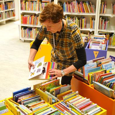 En bibliotekarie radar böcker i en låg låda på bibliotekets barnavdelning.