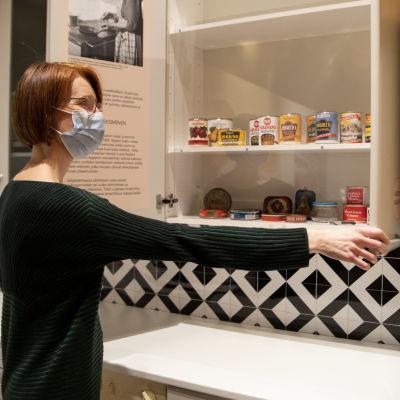 Näyttelyamanuenssi Iina Wahlström kurkistaa kaappiin, jossa on vanhoja säilykepurkkeja.
