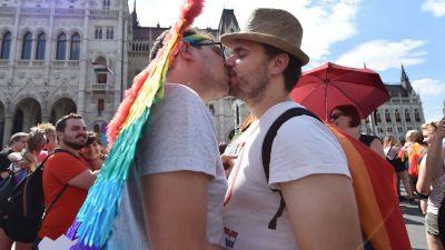 Två männ kysser varandra framför parlamentsbyggnaden i Budapest.