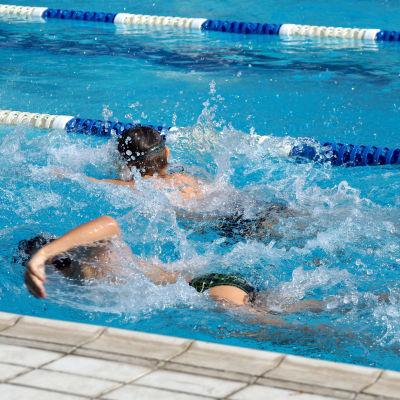 Två barn simmar i en simhall.