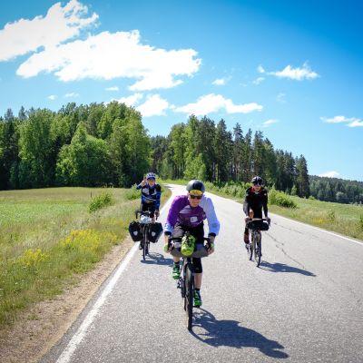 Kolme pyörälijää matkavarusteineen ajaa keskellä tietä.