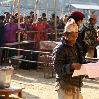 En nepalesisk väljare studerar valsedeln i Chautara, ett hundratal kilometer öster om huvudstaden Katmandu.