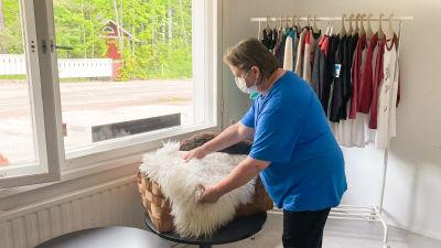 En kvinna i blå t-skjorta rättar till några fårskinn i en korg. Bakom henne syns ett räcke med kläder.