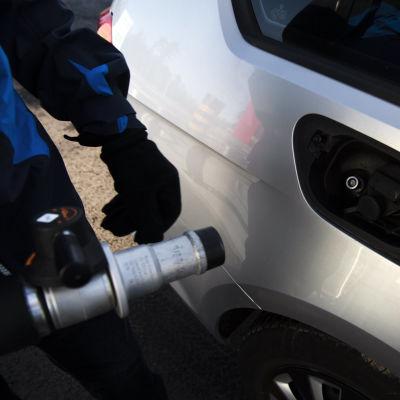 En person håller på att tanka en gasbil.