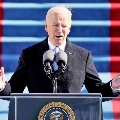 Biden puhuu puhujanpöntön takaa lavalla kongressitalon edustalla. Hän nostaa molempia käsiään.