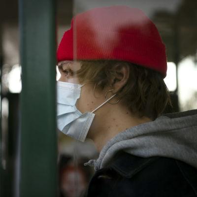 Suojamaskiin pukeutunut nuori bussipysäkillä.