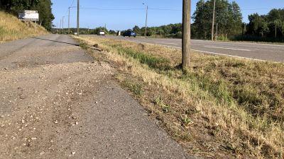 Sand och grus på asfalten på en gång- och cykelväg invid en bilväg. Sommar, solen skiner, ett par bilar syns på vägen.