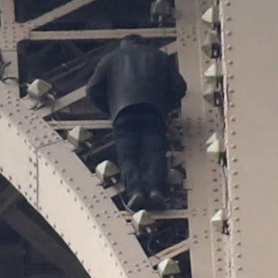 Man klättrar upp längs Eiffeltornet.