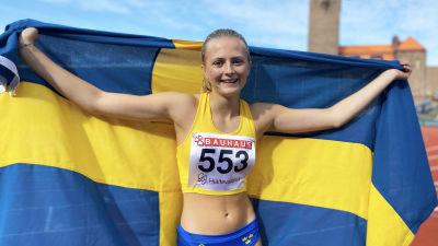 Nora Lindahl poserar på Stockholms stadion draperad i den svenska flaggan.