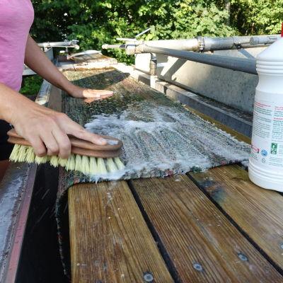 Närbild på matta som tvättas med rotborste och tallsåpa.