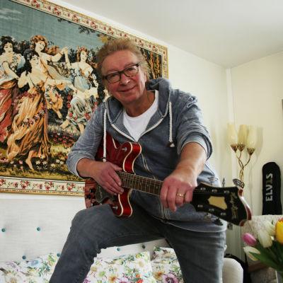 Kisu Jernström poserar i sitt hem i Degerby med en Hagström Viking gitarr