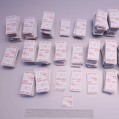 Högar med piller på ett vitt bord. Pillren är inne i plastförpackningar.