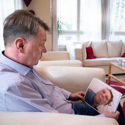 Veijo Kujala i sitt hem i Lundo, med ett foto av sin mamma Vuokko i handen.