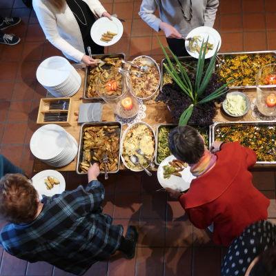 Ett matbuffébord fotat uppifrån med grön sallad, klyftpotatis, såser och andra läckerheter.