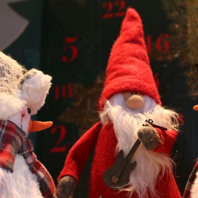 Julgubbe i from av docka med elbas och två snögubbar som tittar på