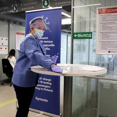 sairaanhoitaja Birgit Salmenhaara puhdistaa pöytää Vaalimaan raja-aseman koronatestauspisteellä.