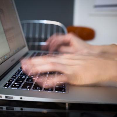 Lähikuva käsistä kirjoittamassa laptopilla.