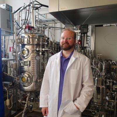 Juha-Pekka Pitkänen klädd i labbrock står i ett laboratorium framför apparatur.