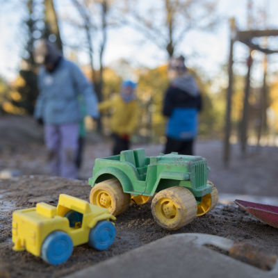 En färgrann spade och platsbilar i en sandlåda väntar på dagisbarn.