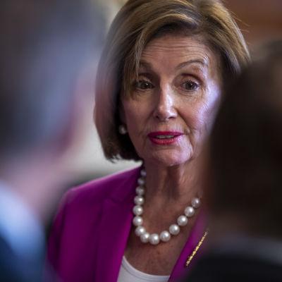 Nancy Pelosi tittar fram mellan två mörkklädda män i förgrunden.