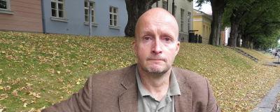 Christer Lindholm, en man utan hår sitter på en bänk vid Aura ås strand.