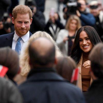 Prinssi Harry ja herttuatar Meghan ihmisjoukon takana. Etualalla pieni Kanadan lippu.