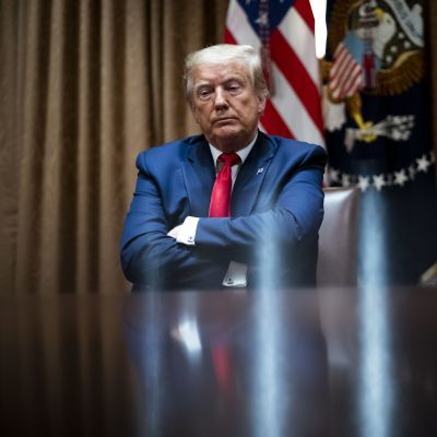 Trump istuu kädet puuskassa Valkoisessa talossa.