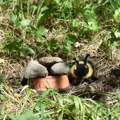 En lerkruka är nergrävd i jorden, den har några stenar ovanpå som tak. En leksakshumla sitter bredvid krukan.